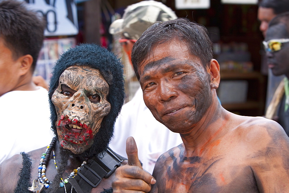 Portrait of two men, one masked, the other with soot smeared on his face during the Ati-Atihan Festival, an annual feast in honour of the Santo Nino, Boracay, Aklan, Philippines, Southeast Asia, Asia - 821-14