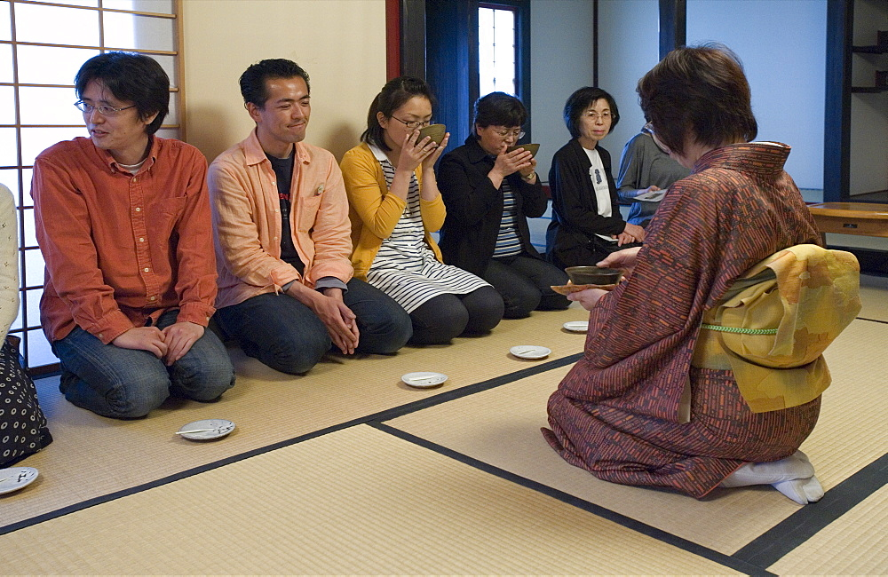 People receiving bowls of tea from the hostess at a Japanese tea ceremony, Japan, Asia - 822-182