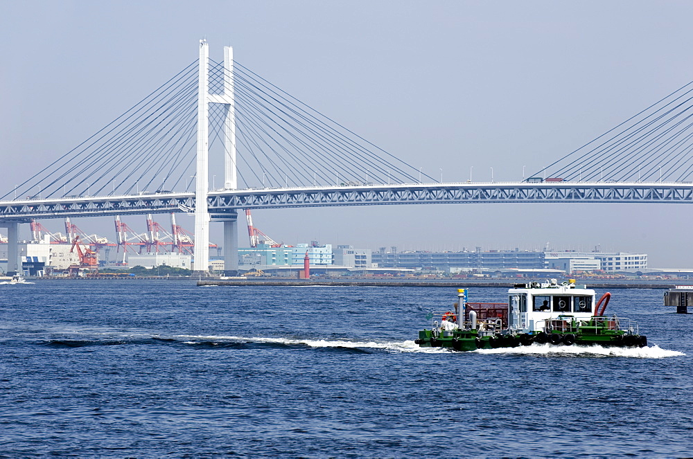 Tug boat passing by the Yokohama Bay Bridge which spans the Tokyo Bay in Yokohama, Japan, Asia - 822-235
