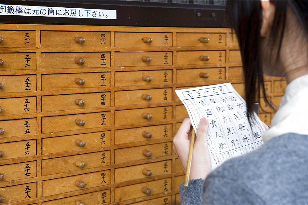 A girl reads her omikuji (paper oracle) at Sensoji Temple in Asakusa, Tokyo, Japan, Asia - 822-244