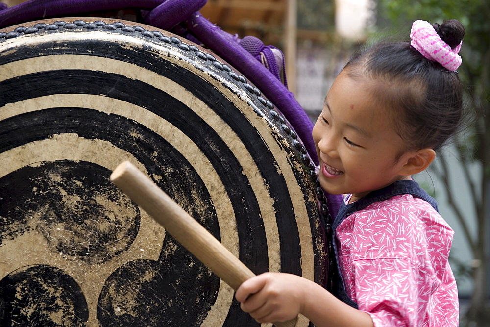 A little girl getting into the spirit of things with a taiko drum at the Sanja Festival in Asakusa, Tokyo, Japan, Asia - 822-289
