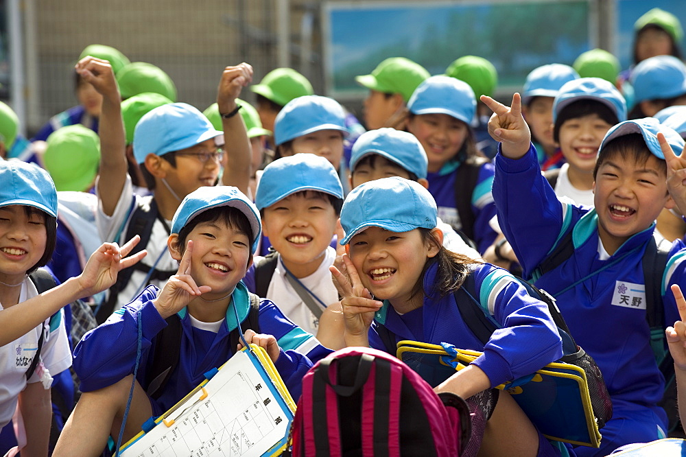 Group of smiling Japanese elementary school children wearing blue and green caps, Japan, Asia