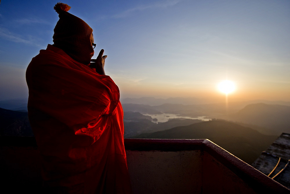 A monk looks out over a sunrise from the top of the sacred mountain Sri Pada (Adam's Peak), Sri Lanka, Asia  - 824-136