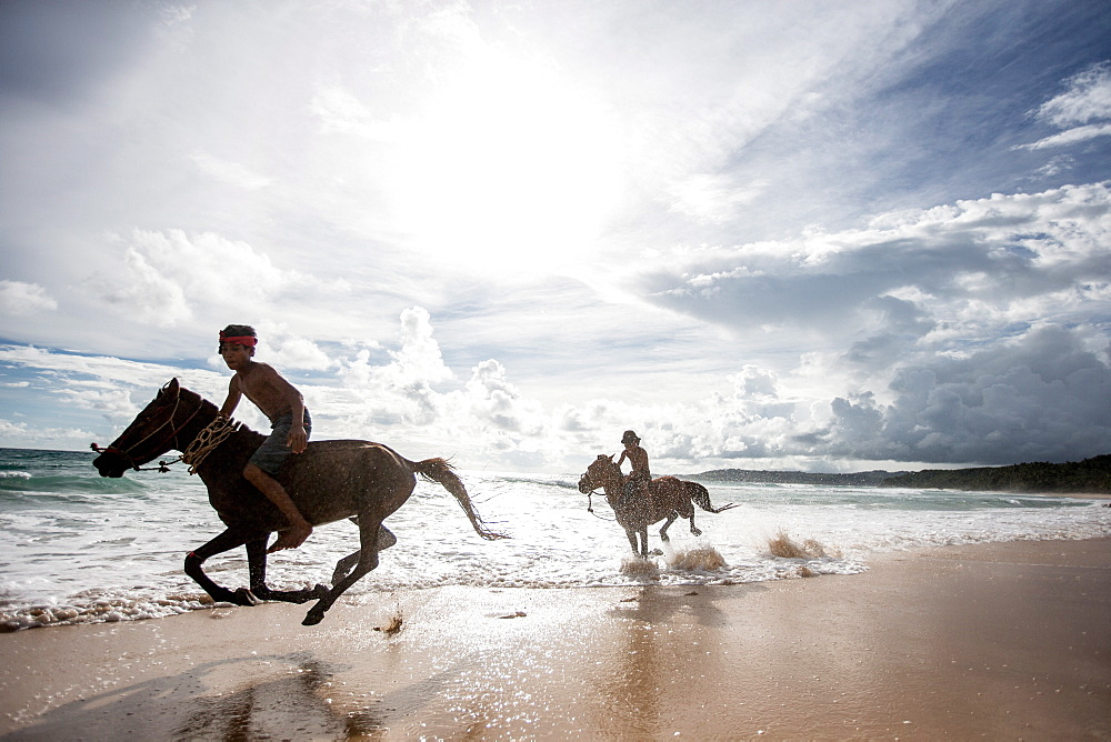 Two young boys and their horses play in the ocean in Nihiwatu, Sumba, Indonesia, Southeast Asia, Asia - 824-146