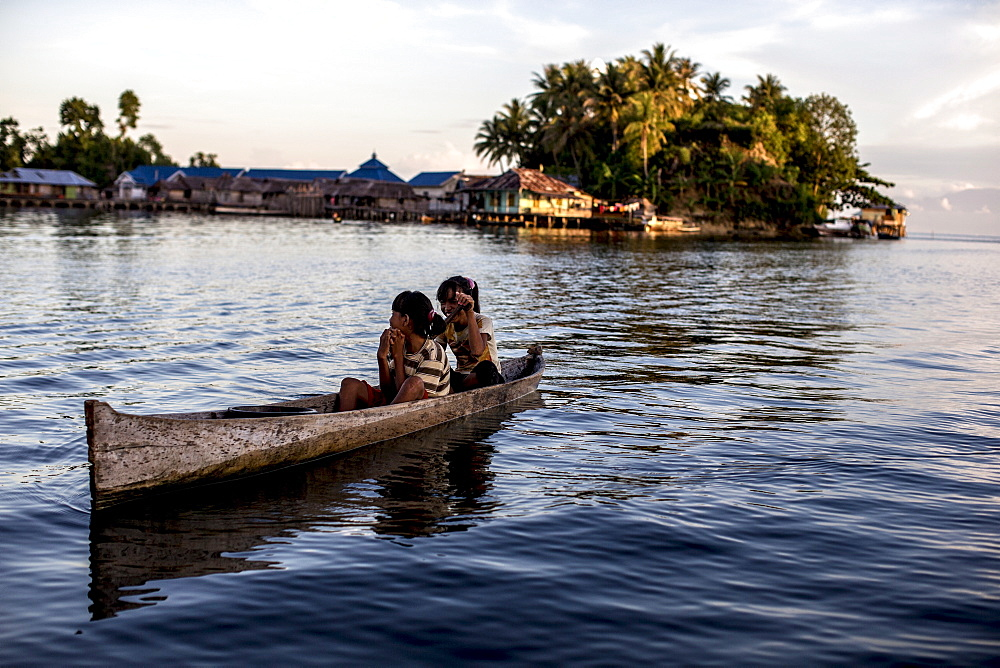 Two girls in a canoe, Togian Islands, Sulawesi, Indonesia, Southeast Asia, Asia