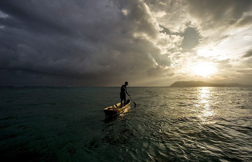 A man in a dug out canoe at sunset, Solomon Islands, Pacific