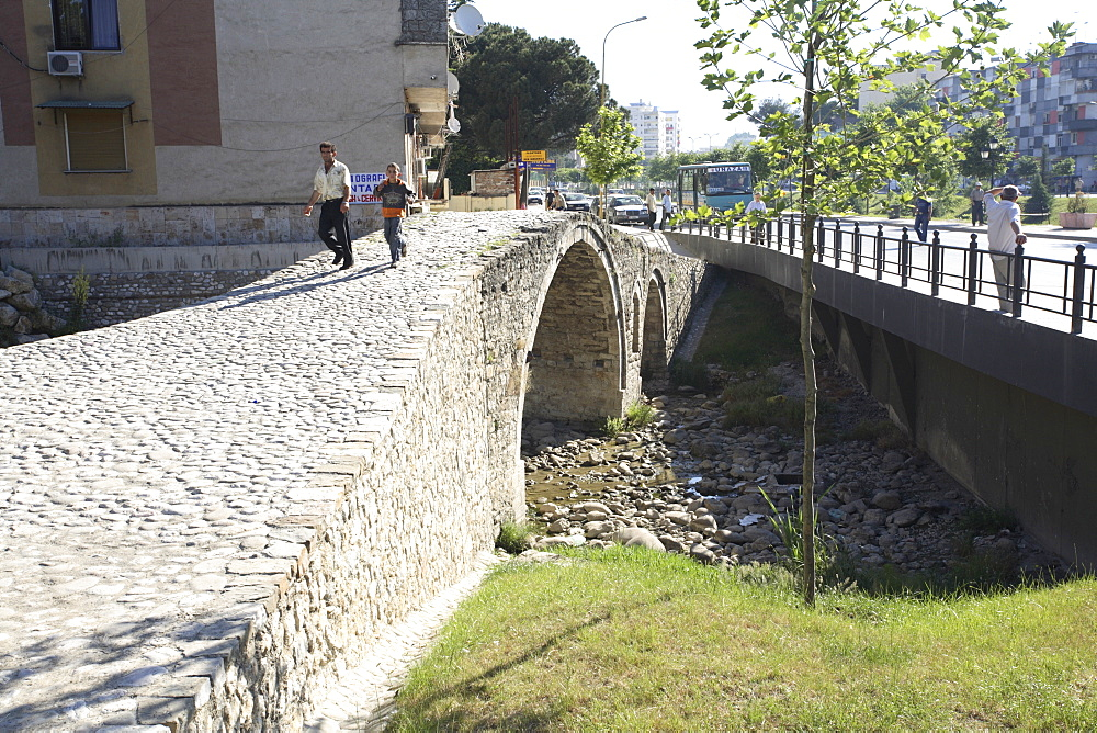 People walking over the Tanner's bridge, an Ottoman stone footbridge in Tirana, Albania, Europe