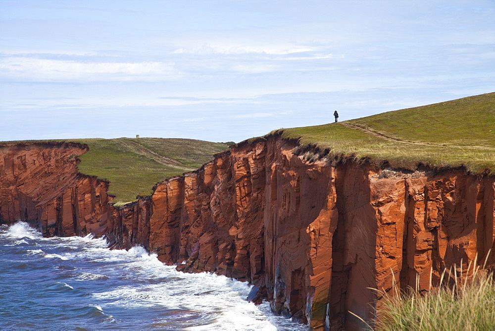 Person walking on red sandstone cliff on Cap-aux-Meules Island in the Iles de la Madeleine (Magdalen Islands), Quebec, Canada, North America - 825-194