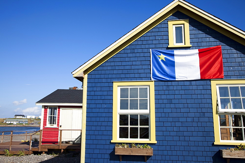 Acadian flag on blue house in La Grave, Ile Havre-Aubert, one of the Iles de la Madeleine (Magdalen Islands), Gulf of St. Lawrence, Quebec, Canada, North America - 825-202