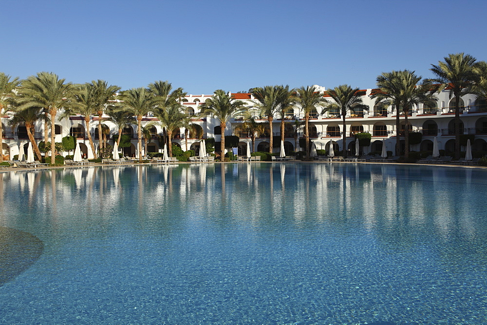 Rooms with verandas overlook a palm fringed swimming pool within the Royal Savoy Resort at Sharm el-Sheikh, Egypt, North Africa, Africa