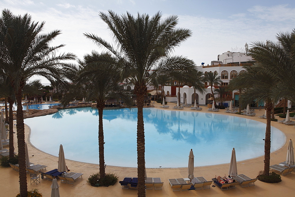 A palm fringed swimming pool within the Royal Savoy Resort at Sharm el-Sheikh, Egypt, North Africa, Africa