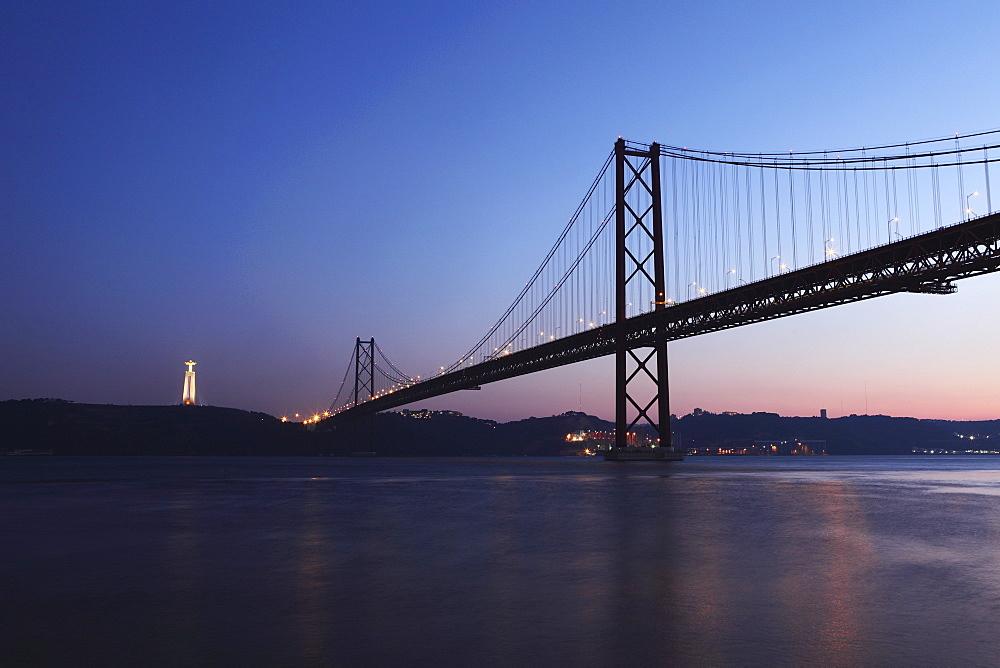 The 25 April Suspension Bridge at dusk over the River Tagus (Rio Tejo), Christus Rei is illuminated at Almada, Lisbon, Portugal, Europe