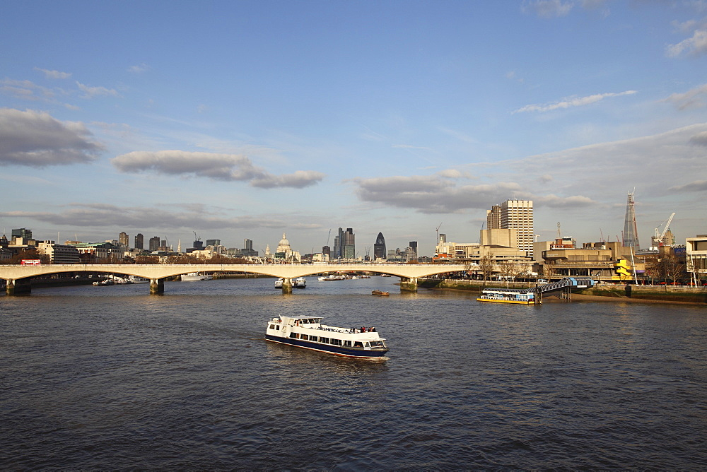 A cruise boat on River Thames, ahead of Waterloo Bridge and the skyline of the City, from Westminster, London, England, United Kingdom, Europe