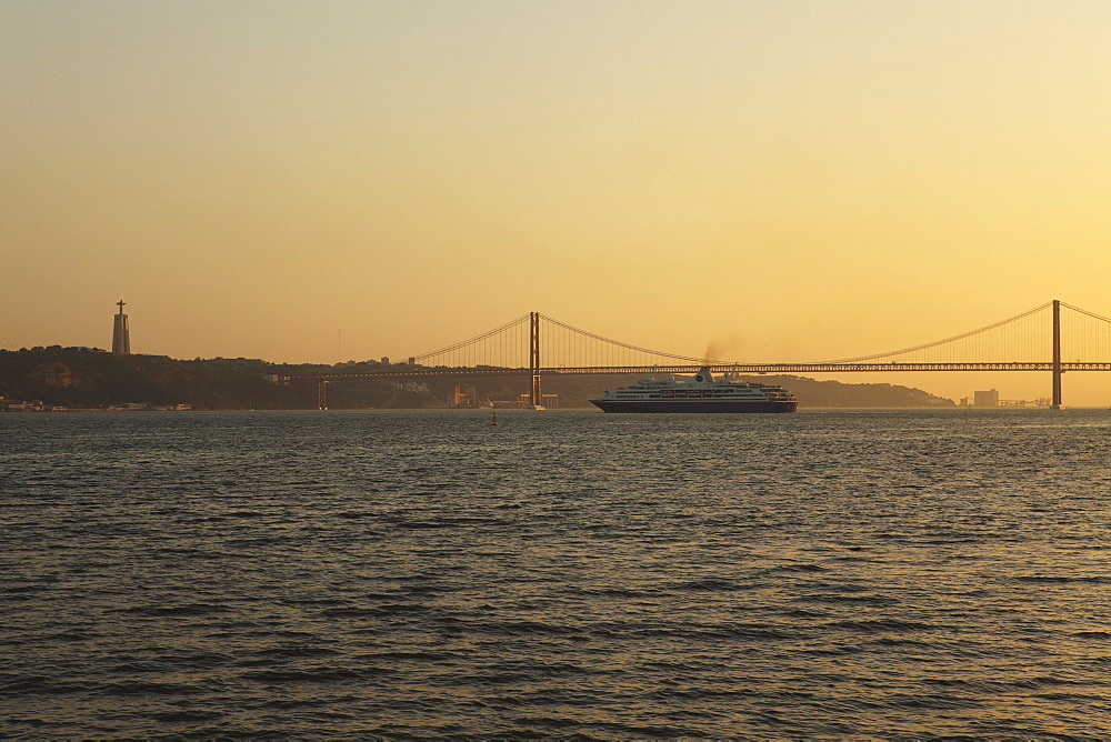 A cruise liner turns into the sunset, on the River Tagus under the 25 April Bridge and Christus Rei statue, Lisbon, Portugal, Europe