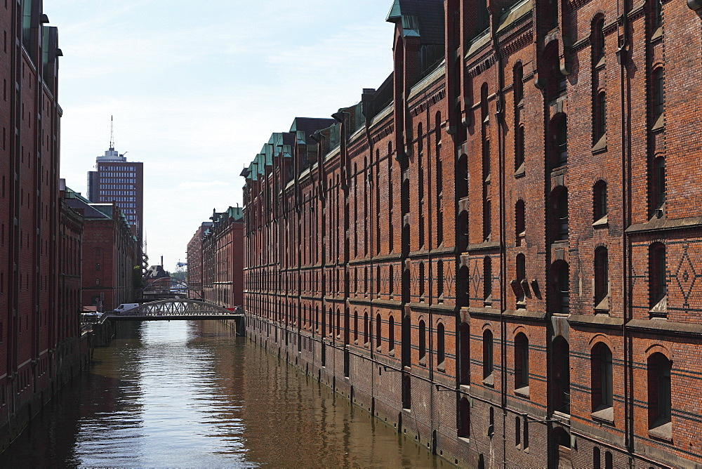 Red brick warehouses overlook a canal in the Speicherstadt district, once a duty free port, in Hamburg, Germany, Europe - 826-583