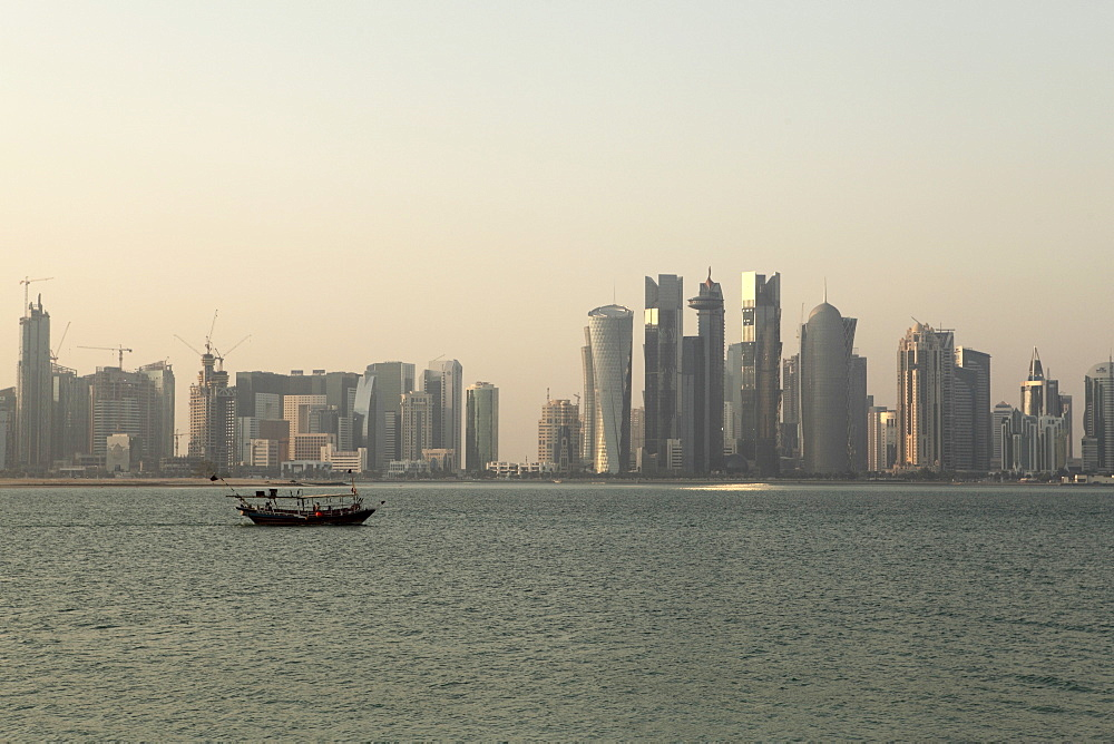 A traditional wooden dhow boat sails past modern skyscrapers in the West Bay financial district of Doha, Qatar, Middle East
