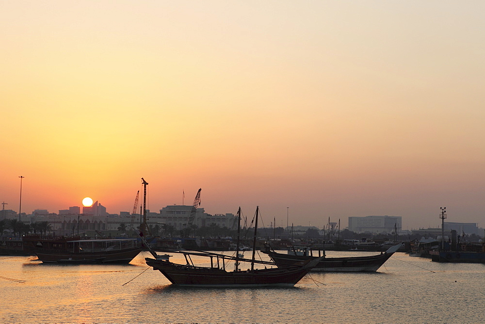 Traditional wooden dhow boats in the Corniche marina, at sunset in Doha, Qatar, Middle East - 826-589