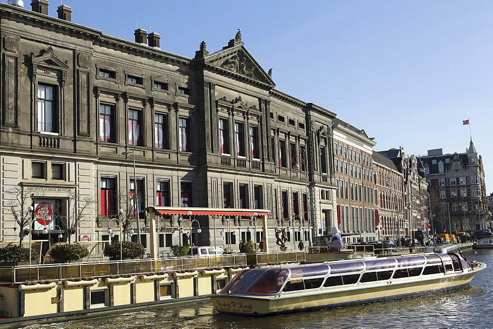 A sightseeing boat by the Allard Pierson Museum on the Rokin canal in central Amsterdam, Netherlands, Europe - 826-623