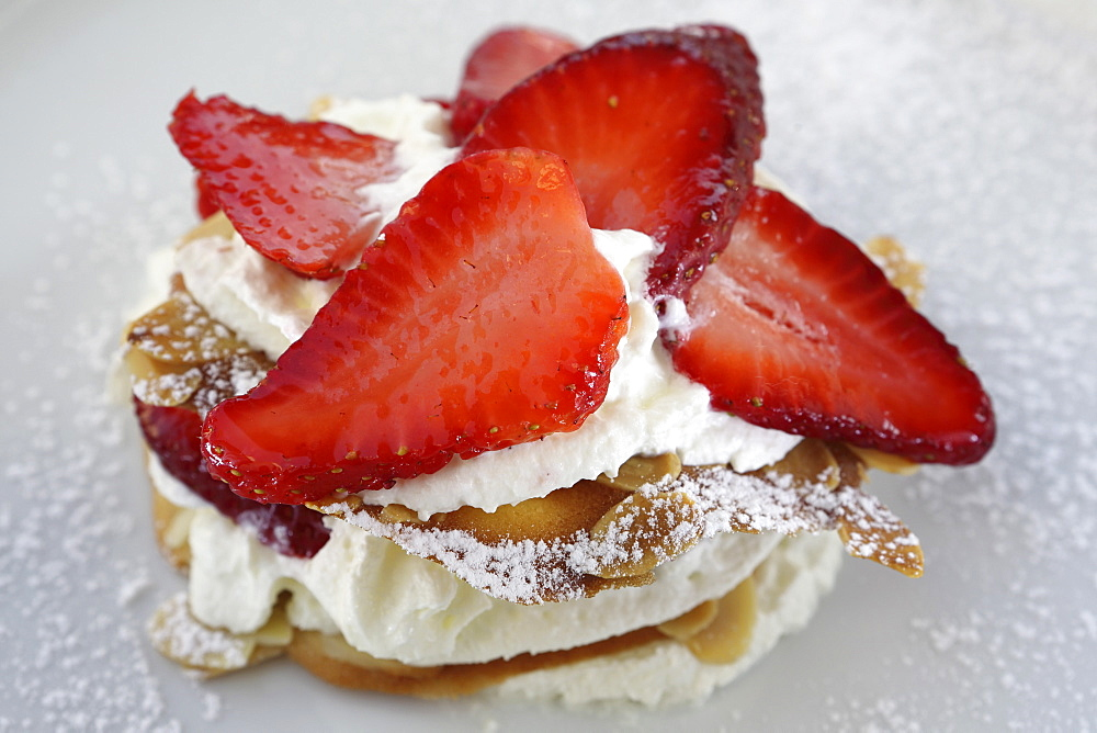 A dessert of strawberries served with cream, cream panna and almond biscuit in Monopoli, Apulia, Italy, Europe