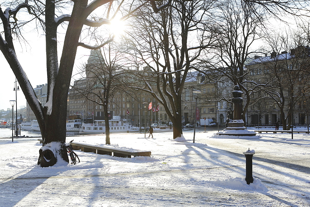 Sunshine in the snow-covered Berzelii Park, by the waterfront at Nybroviken, in Stockholm, Sweden, Scandinavia, Europe - 826-661