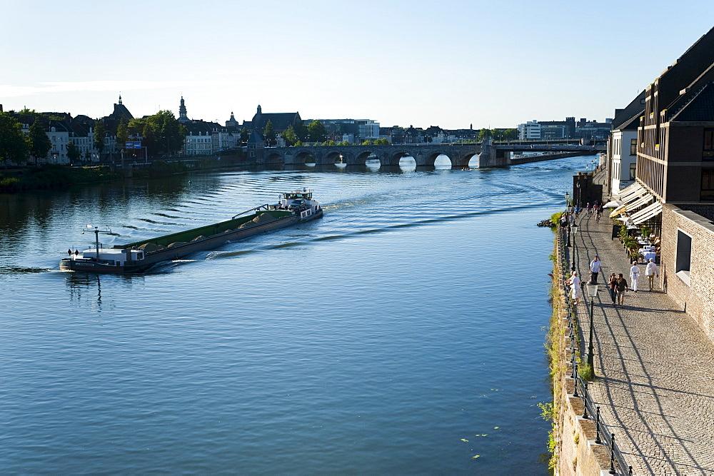 Barge on the River Maas, St. Servatius Bridge and coffee bars at Maaspuntweg riverfront, Maastricht, Limburg, The Netherlands, Europe
