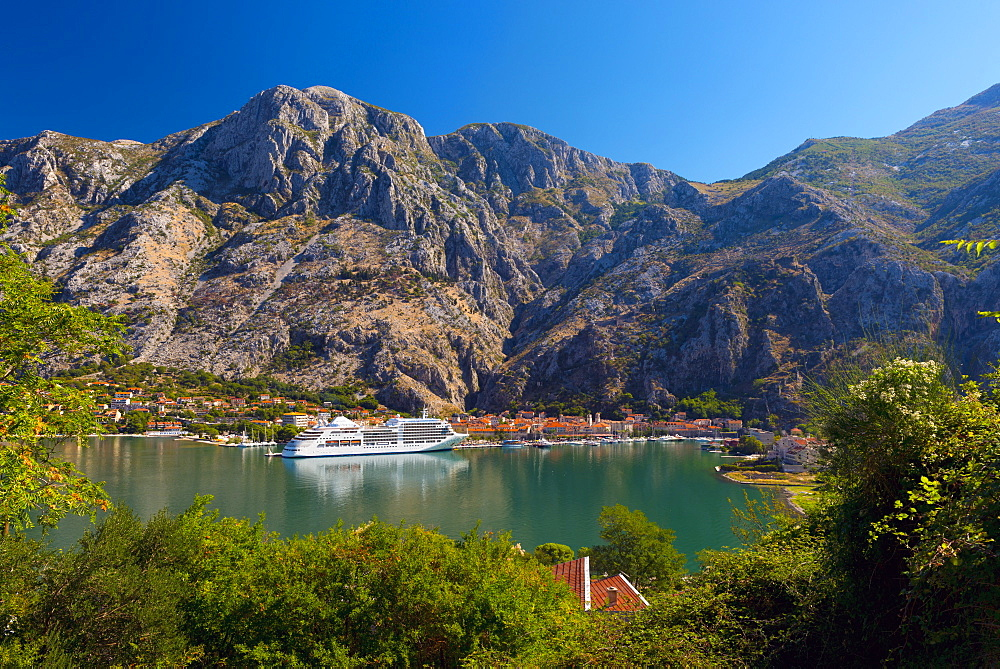 Cruise ship dwarfs the Old Town (Stari Grad), Kotor, Bay of Kotor, UNESCO World Heritage Site, Montenegro, Europe