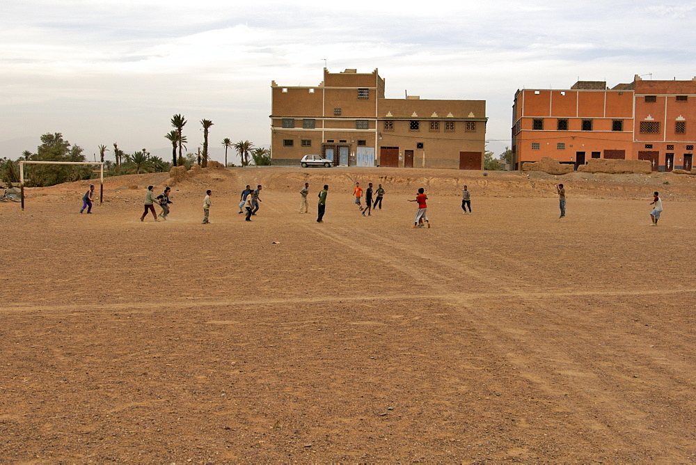 Moroccan children playing football outside a village in the Dades valley in Morocco