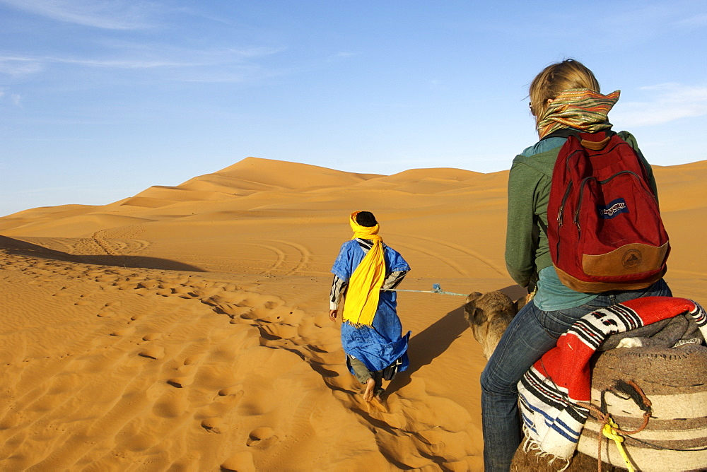 A berber man in traditional outfit leads a woman on a camel through the dunes of Erg Chebbi on the periphery of the Sahara desert in eastern Morocco