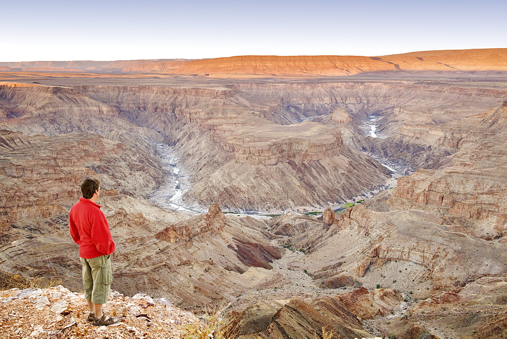 A man stands looking out across the Fish River Canyon in southern Namibia at dawn, Namibia, Africa