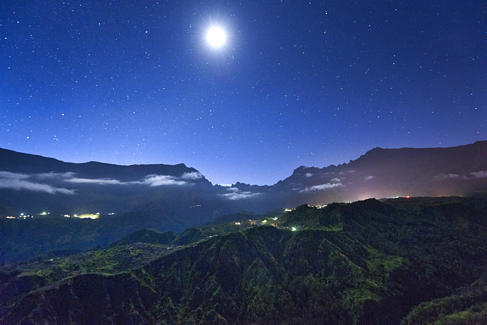 Night view of stars and the moon above the Cirque de Cilaos caldera on the French island of Reunion in the Indian Ocean, Africa