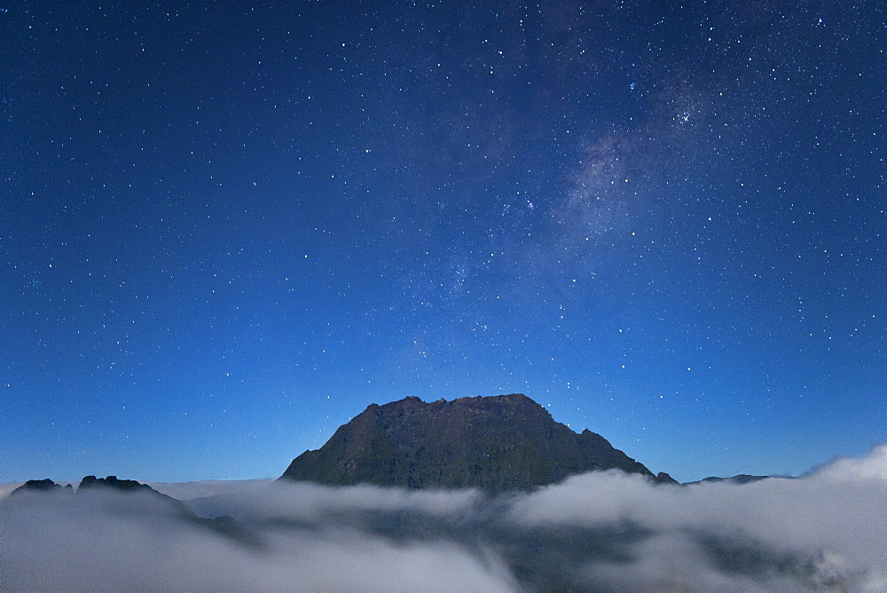Night-time view of a mountain peak poking above the clouds on the French island of Reunion in the Indian Ocean, Africa