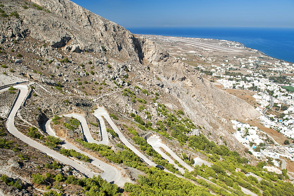 The winding road leading from Kamari to the ruins of Ancient Thira on Messavouno mountain on the Greek island of Santorini, Cyclades, Greek Islands, Greece, Europe