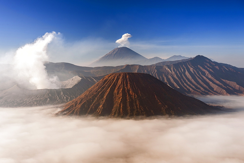 Mount Bromo (venting steam, left) and Gunung Semeru (centre background) in Bromo Tengger Semeru National Park, Java, Indonesia.
