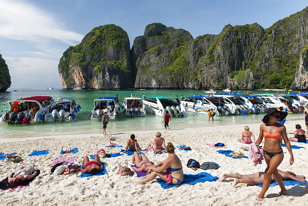 Tourist boats and tourists in Maya Bay on Koh Phi Phi Ley island in Thailand.