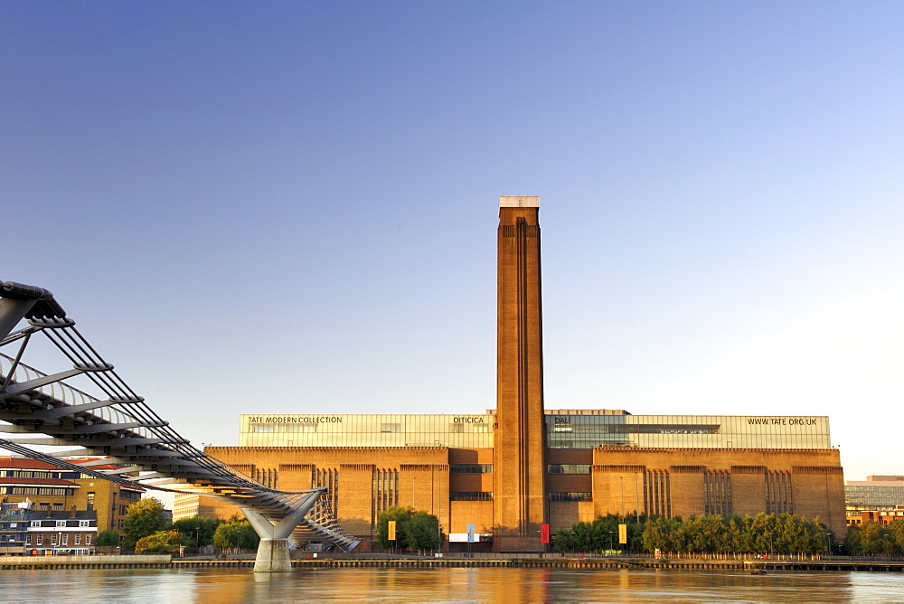 Early morning view of the Tate Modern art Gallery and Millenium Bridge taken from across the Thames River in London. The Tate Modern is the converted former Bankside power station on the south bank of the Thames River. It was built in two phases between 1947 and 1963 and was designed by Sir Giles Gilbert Scott.