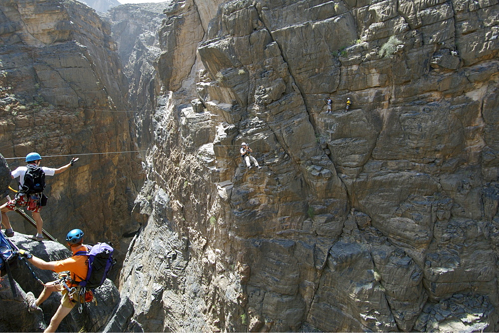 A hiker traversing a zip-wire (aka flying fox) on the Via Ferrata hike in Snake Canyon, part of Wadi Bani Auf in Jebel Akhdar of the western Hajar mountains in Oman.