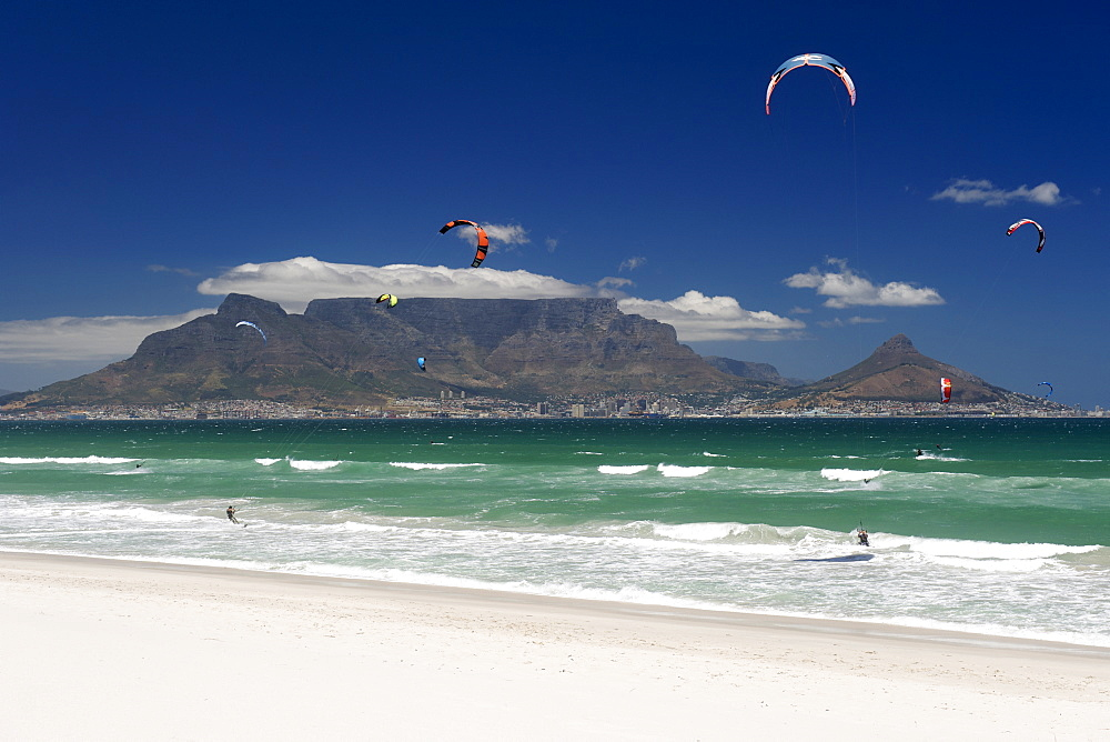 Kite surfers at Blouberg Beach with a view of Table Mountain and the city of Cape Town visible across Table Bay.