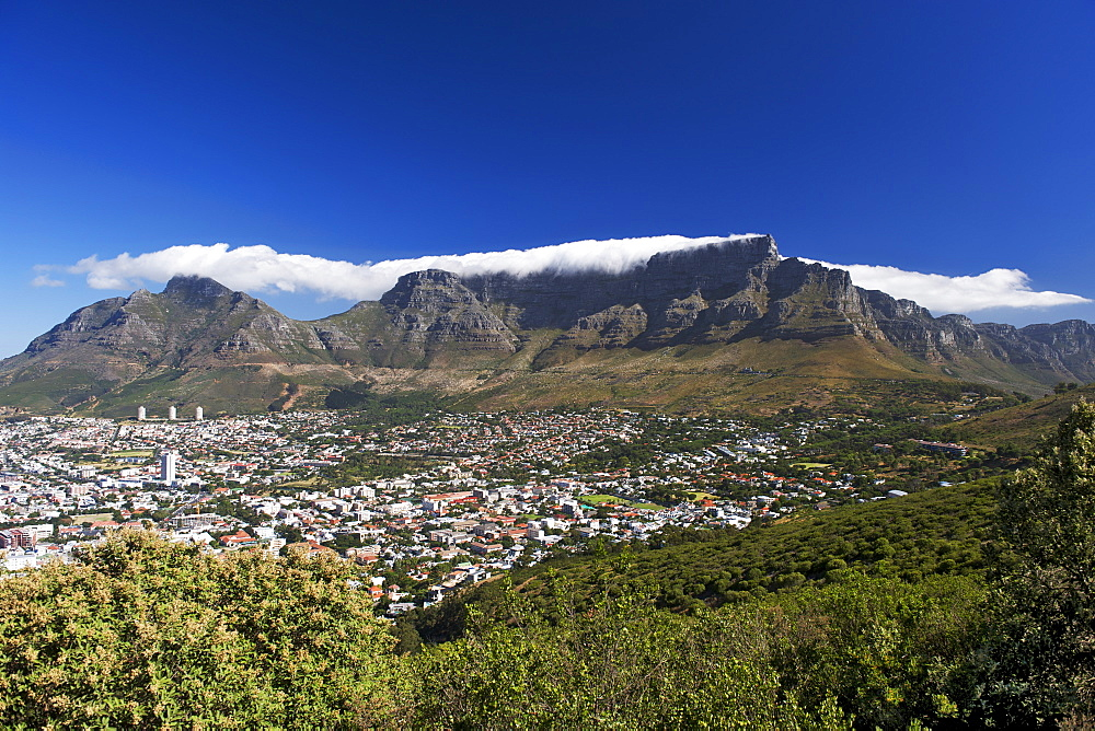 View of the city of Cape Town surrounded by Table Mountain on which the clouds form the well-known 'table cloth'.