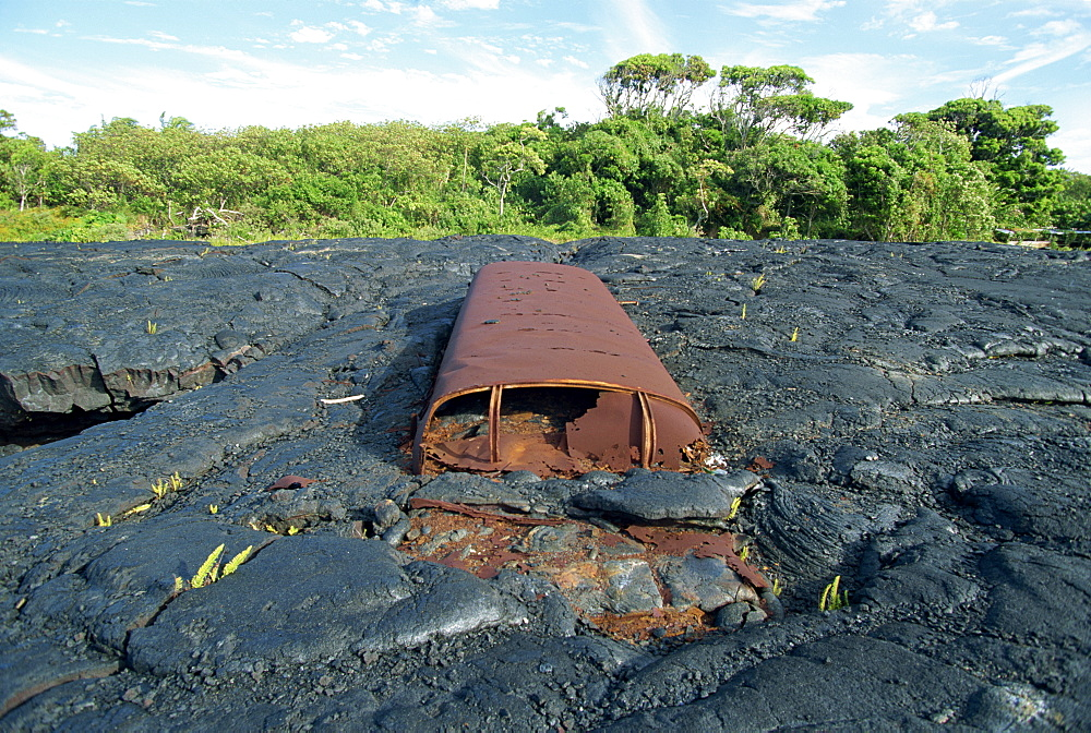 School bus near Kaimu buried in the 1988 basalt lava flows that covered a large area of the south east Puna coast and cut highway 130, Big Island, Hawaii, United States of America, North America
