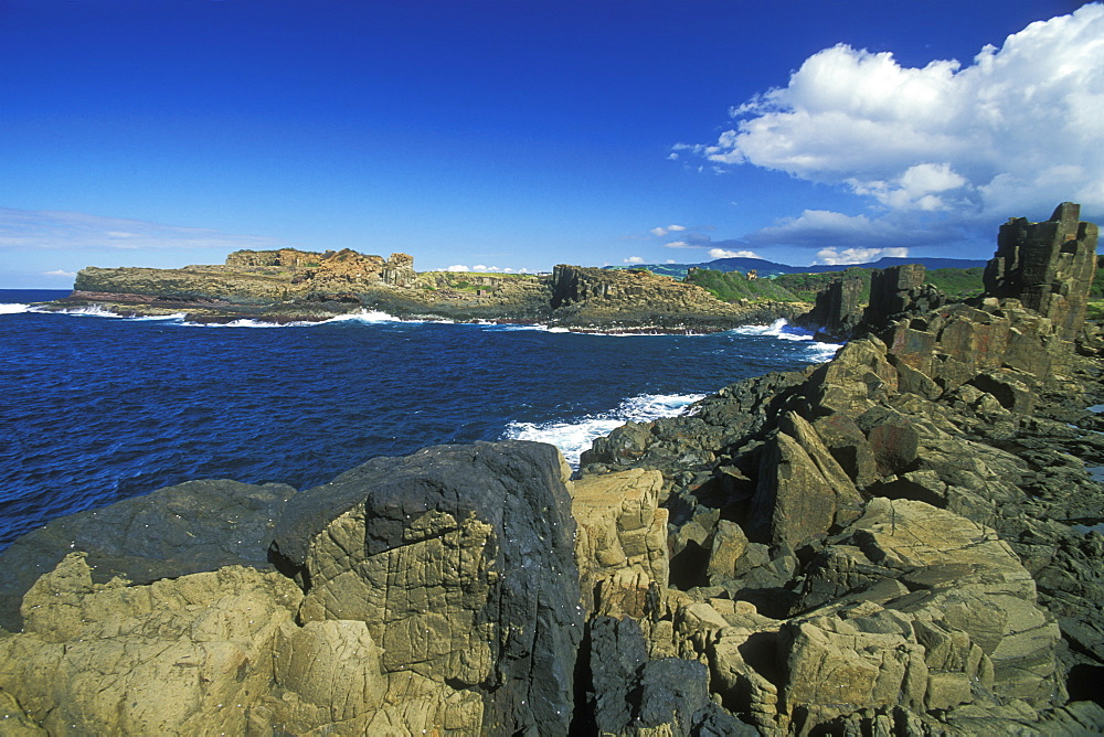 Columnar structures, created during cooling of basalt lava, with an intrusion or dyke of darker rock in the foreground, near Bombo Beach, Kiama, south coast, New South Wales, Australia, Pacific