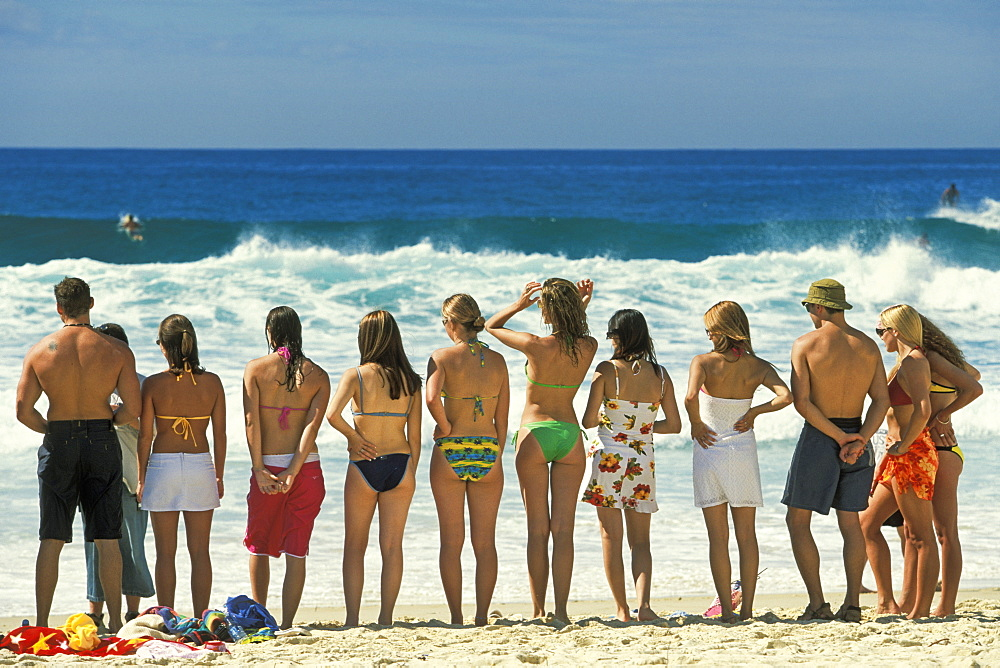Attractive young people in swim wear lined up for a photo on Sydney's iconic Bondi Beach in the Eastern Suburbs, Bondi, New South Wales, Australia, Pacific
