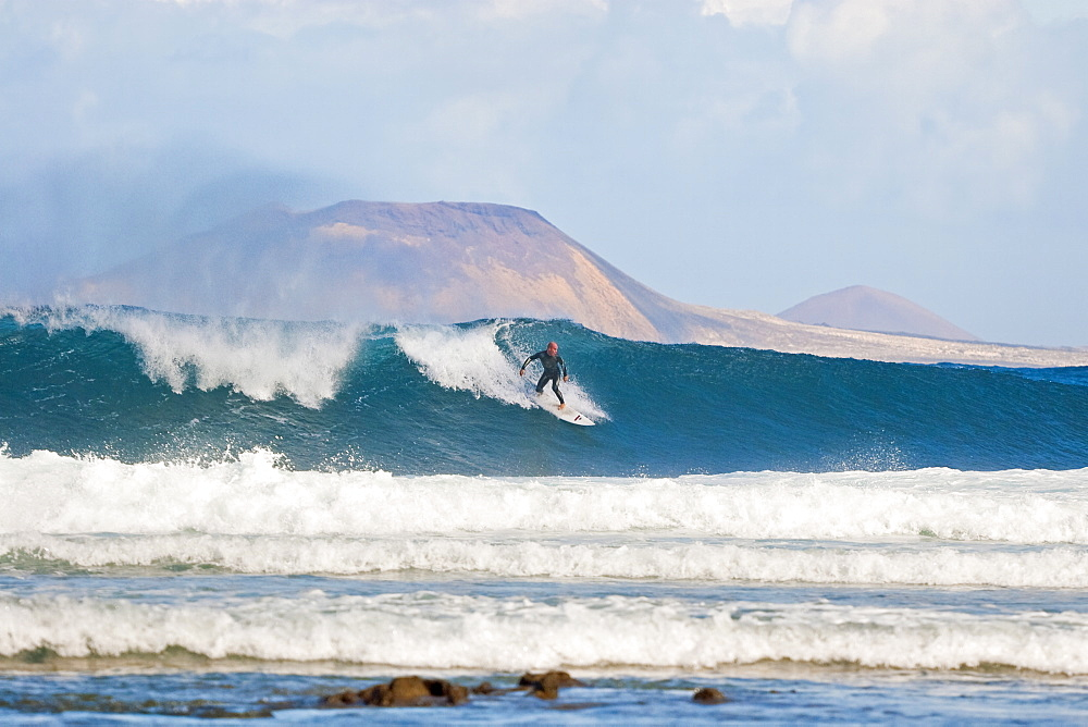Surfer on a large wave with Graciosa Island beyond, at the world class surf reef break known as San Juan, east of Famara in the north of the island, Famara, Lanzarote, Canary Islands, Spain, Atlantic, Europe - 83-12401