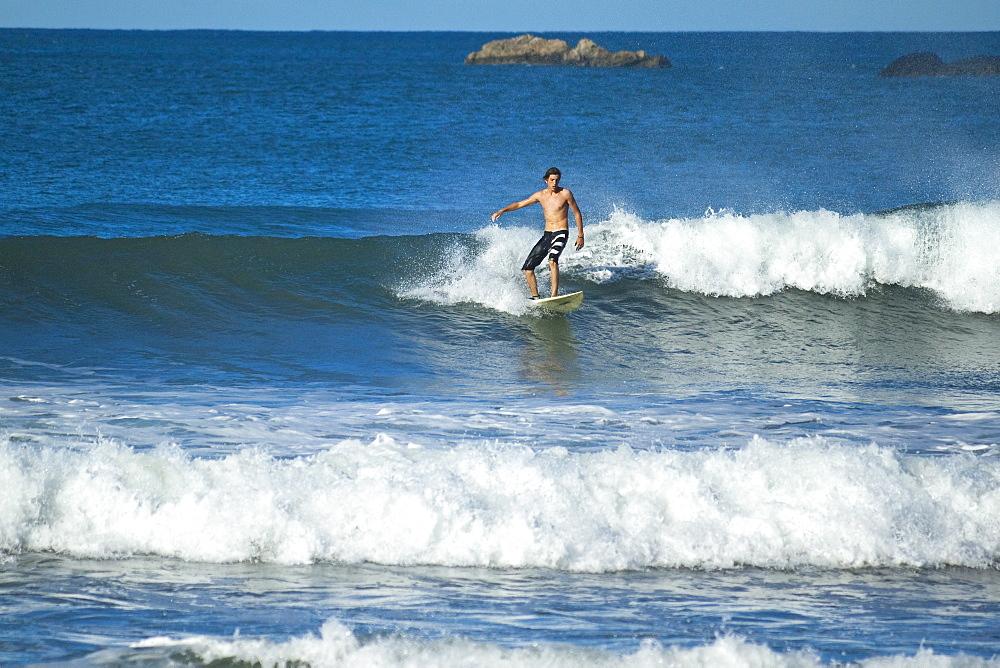 Surfer on a wave, Playa Guiones beach, Nosara, Nicoya Peninsula, Guanacaste Province, Costa Rica, Central America