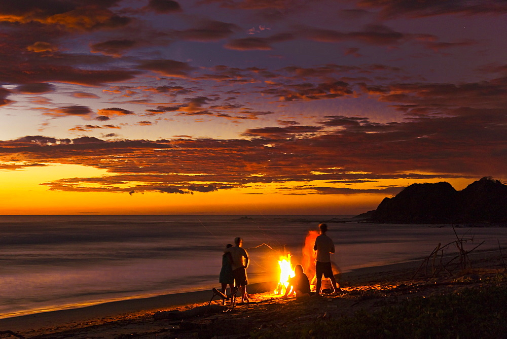 People with driftwood fire at sunset on Playa Guiones beach, Nosara, Nicoya Peninsula, Guanacaste Province, Costa Rica