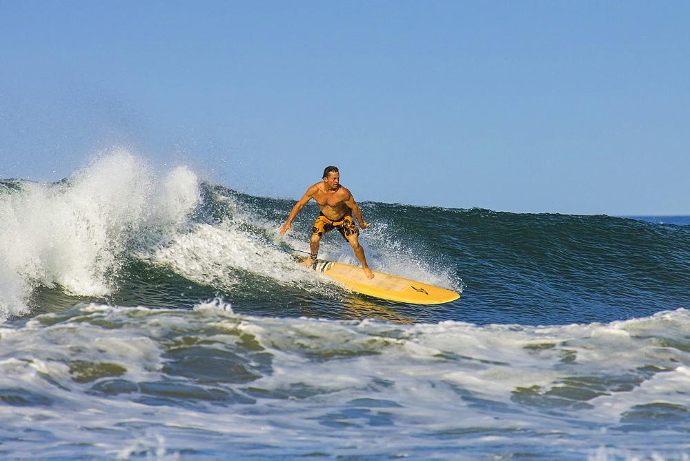 Surfer on longboard riding wave at popular Playa Guiones surf beach, Nosara, Nicoya Peninsula, Guanacaste Province, Costa Rica, Central America