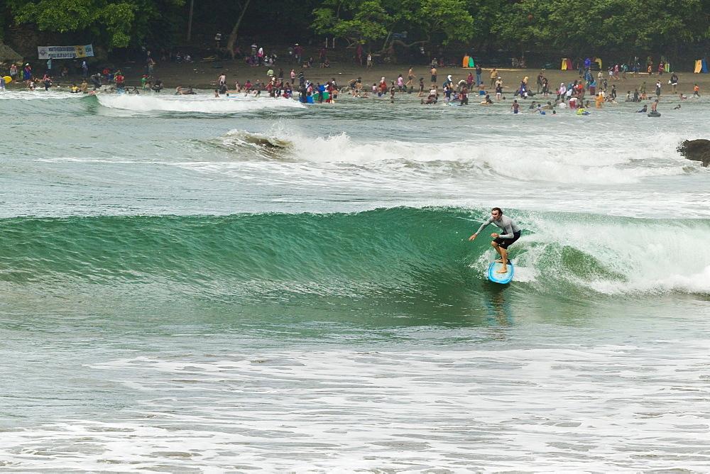 Surfer on a wave at this popular point break surf spot and small resort, Batu Karas, near Pangandaran, West Java, Java, Indonesia, Southeast Asia, Asia