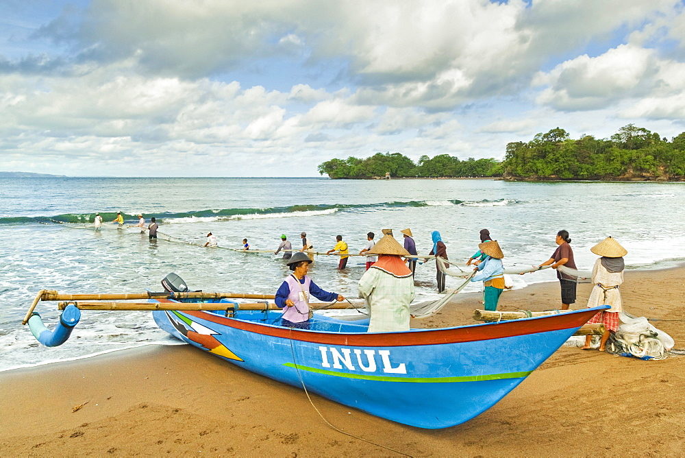 Outrigger fishing boat and people pulling net in by hand to shore near Batu Karas, Pangandaran, West Java, Java, Indonesia, Southeast Asia, Asia