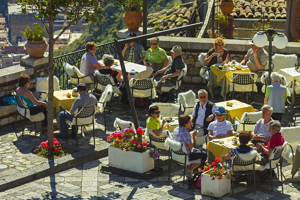 People alfresco on cafe terrace in spring at this pretty village high over Taormina, Castelmola, Catania Province, Sicily, Italy, Europe