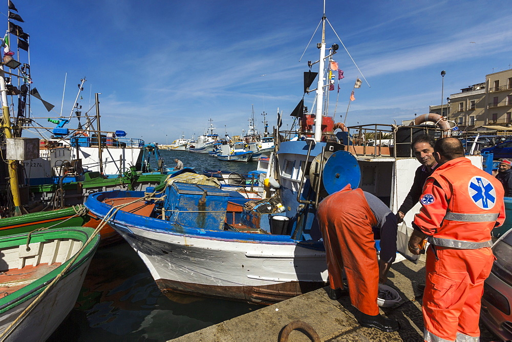 Fishermen and trawlers in the bustling port district of this major north western historic fishing town, Trapani, Sicily, Italy, Mediterranean, Europe