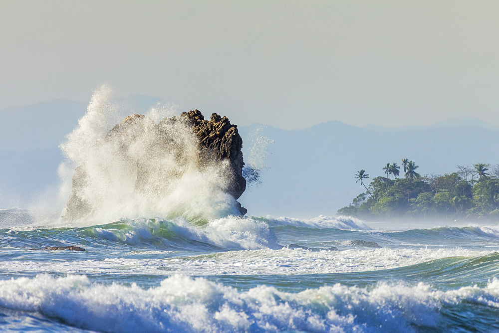 Surf on a sea stack between Santa Teresa and Hermosa beaches, far south Nicoya Peninsula, Santa Teresa, Puntarenas, Costa Rica, Central America